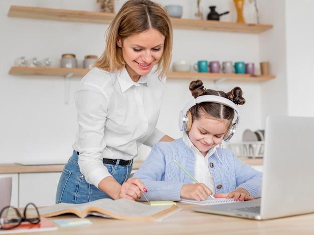 Mãe ajudando a filha em uma aula on-line