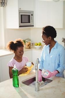Mãe, ajudando a filha na limpeza de utensílios