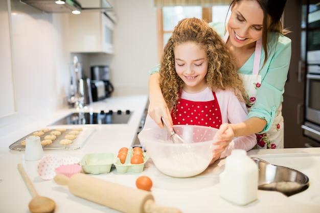 Mãe ajudando a filha no mexendo farinha na cozinha