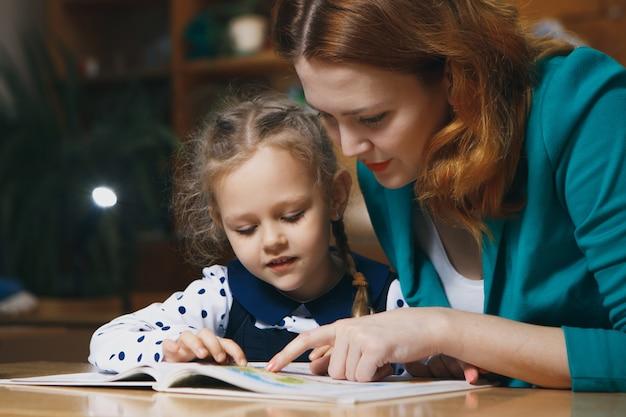 Mãe ajudando criança depois da escola. pré-escolar fazendo lição de casa com a ajuda do tutor. conceito de ensino em casa.