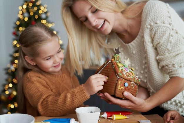 Mãe ajudando crianças a decorar uma casa de pão de gengibre