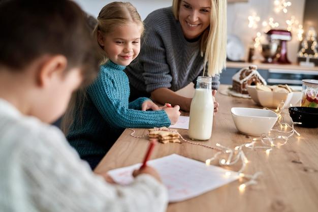 Mãe ajudando crianças a escreverem cartas para o papai noel