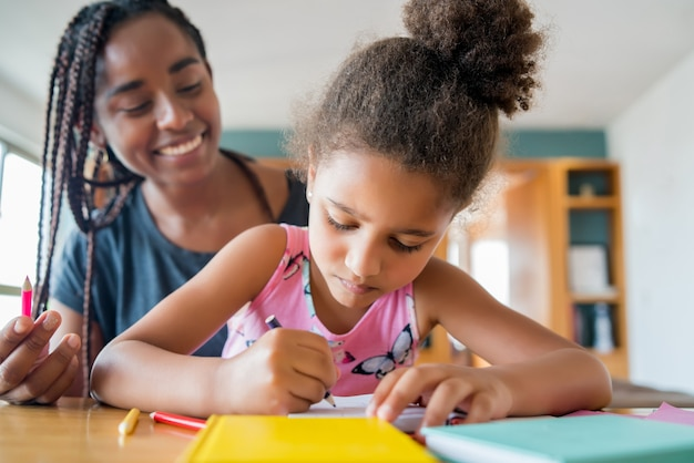 Mãe ajudando e apoiando a filha com as aulas em casa enquanto fica em casa