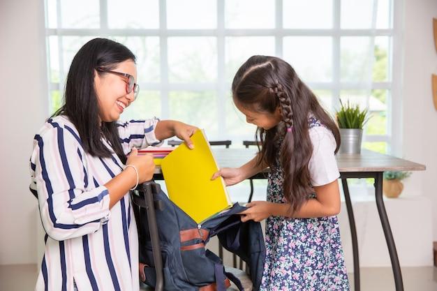 Mãe, ajudando, escola primária, menina, embalagem, livros, para, a, sacolas