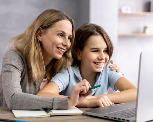 Mãe ajudando filha a estudar