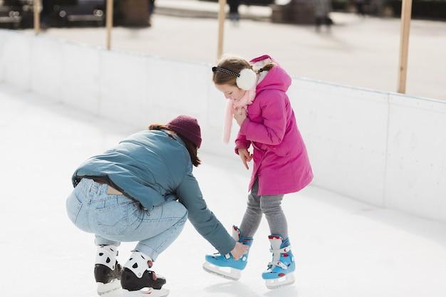 Mãe ajudando filha cheia tiro