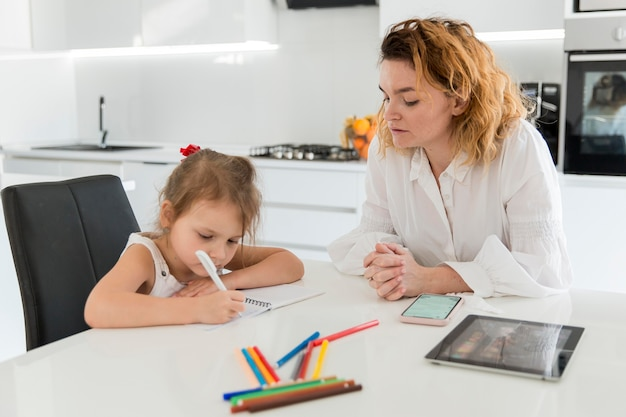 Mãe ajudando filha com lição de casa
