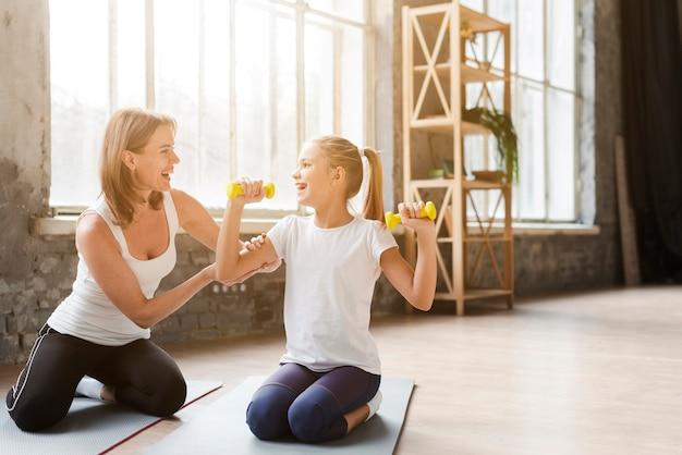 Mãe ajudando filha segurando pesos no tapete de ioga