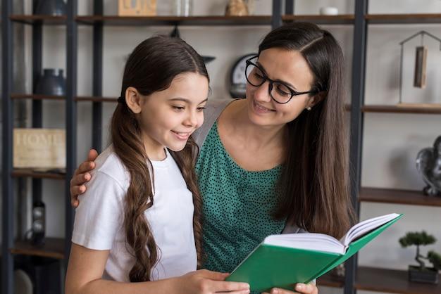 Mãe ajudando menina a ler