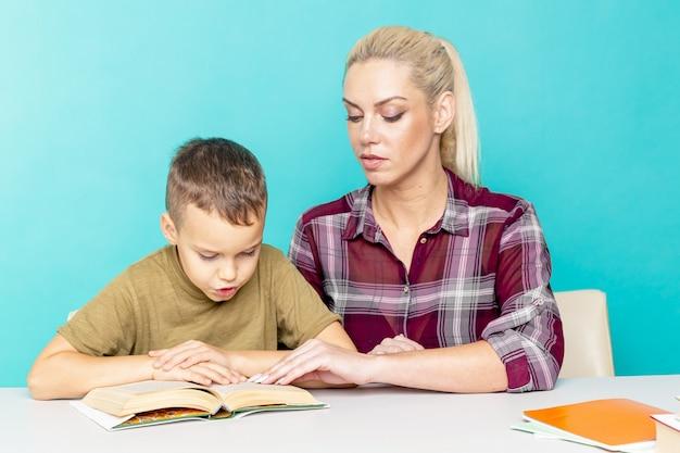 Mãe ajudando o filho com a lição de casa sobre fundo rosa isolado. educação a distância.