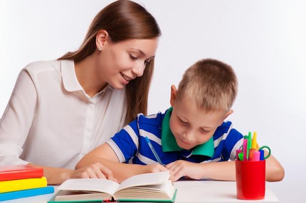Mãe ajudando o filho com lição de casa na mesa
