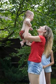 Mãe alegre abraçando seu bebê depois de nadar na piscina