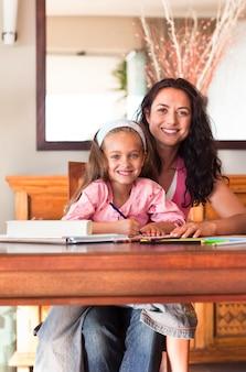 Mãe alegre ajudando sua filha a fazer a lição de casa