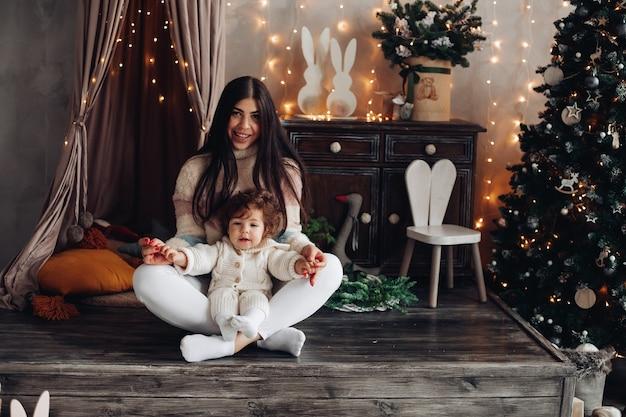 Mãe alegre brinca com seu filho pequeno na atmosfera de natal na sala