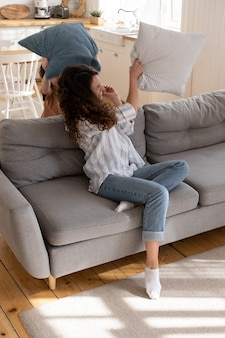 Mãe alegre e criança brincalhona brincando na sala de estar cheia de alegria, sentadas no sofá em casa