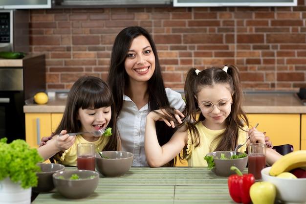 Mãe alegre e duas filhas estão comendo salada saudável juntos em casa. o conceito de alimentação saudável, valores familiares, tempo juntos
