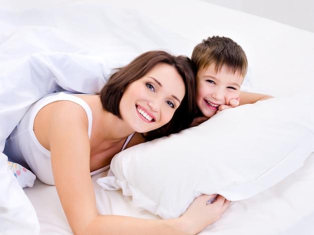 Mãe alegre e feliz e seu lindo filho deitado em uma cama