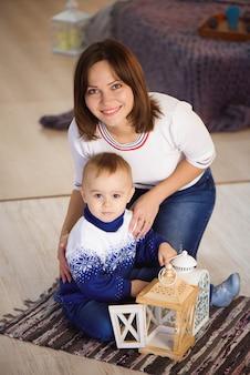 Mãe alegre e seu filho lindo filho se divertindo perto de árvore dentro de casa. família amorosa na sala de natal.