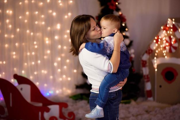 Mãe alegre e seu filho lindo filho se divertindo perto de árvore dentro de casa