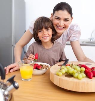 Mãe alegre e seu filho tomando café da manhã