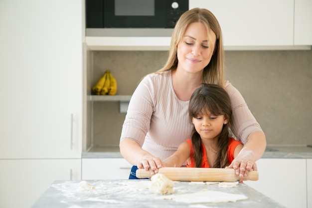 Mãe alegre e sua filha cozinhando juntas, rolando massa na mesa da cozinha com farinha em pó.