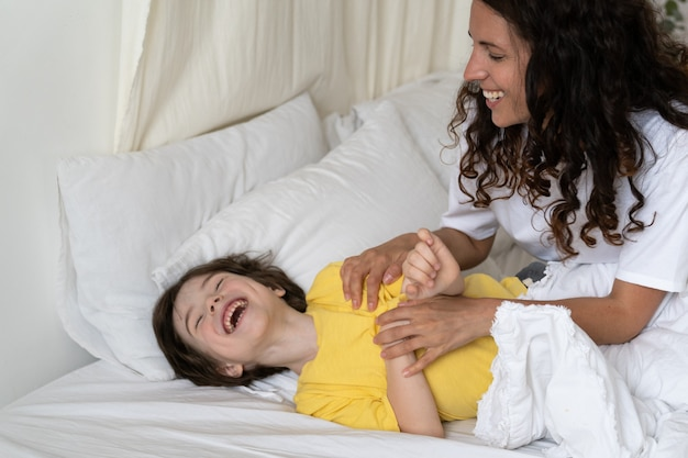 Mãe alegre fazendo cócegas filho na cama na manhã mãe acordando criança com jogo alegre no fim de semana