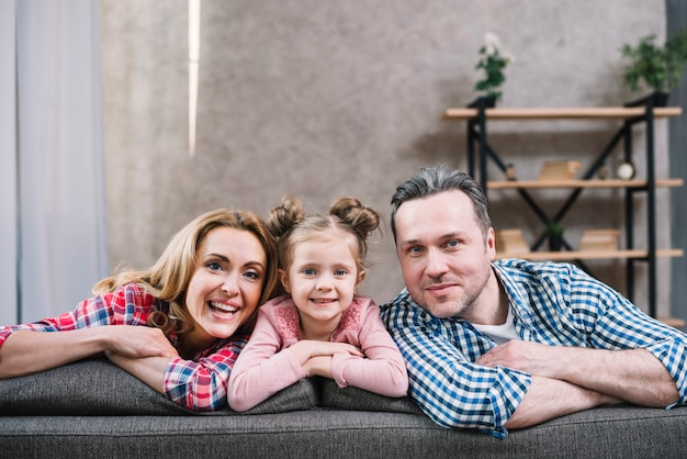 Mãe alegre; filha e pai sentado no sofá olhando para a câmera