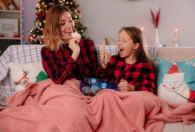 Mãe alegre segura batatas fritas e gesticula para esperar a filha de olhos fechados coberto com um cobertor sentada no sofá e curtindo o natal em casa