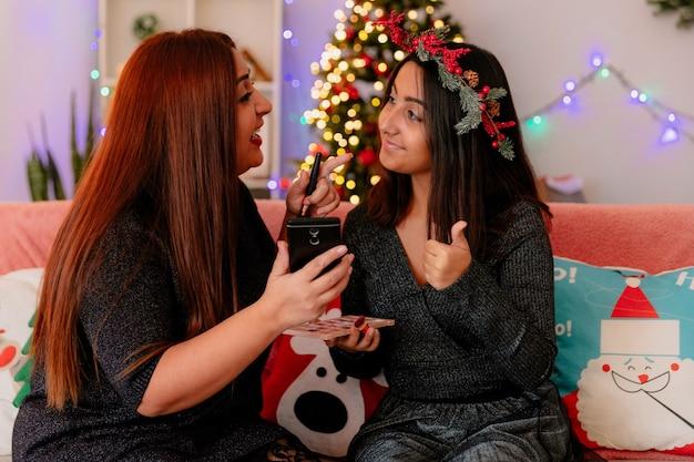 Mãe alegre segura o telefone e olha para a filha dedilhando-se sentada no sofá, aproveitando o natal em casa
