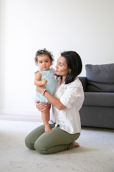Mãe alegre sentada no chão em casa, segurando a doce filha nos braços. tiro vertical. conceito de paternidade e infância