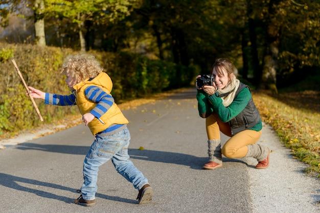 Mãe alegre tirando foto de seu lindo filho pequeno no parque,