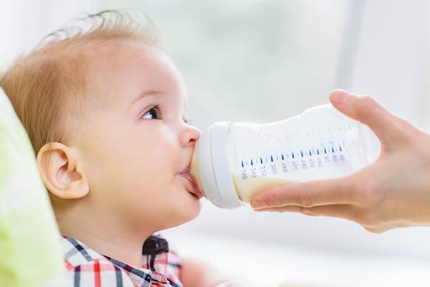 Mãe alimenta bebê de uma garrafa de leite