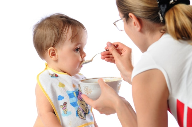 Mãe alimenta menina com colher
