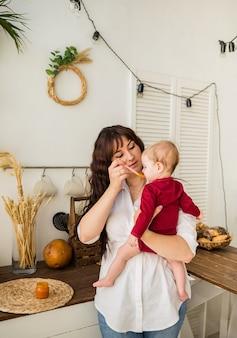Mãe alimenta menina com purê de cenoura na cozinha de casa