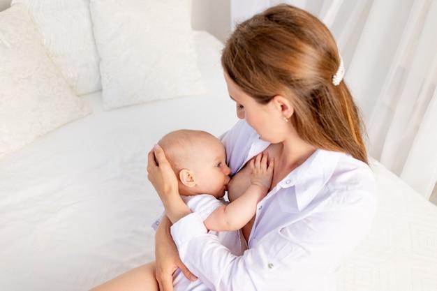 Mãe alimenta o bebê 6 meses de mama, sentado em uma cama branca em casa