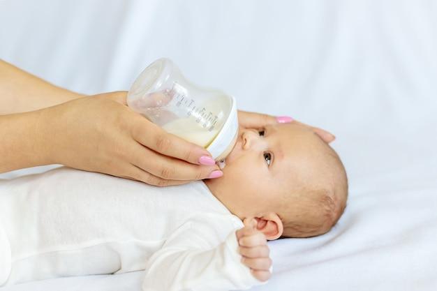 Mãe alimenta seu bebê recém-nascido com uma mamadeira