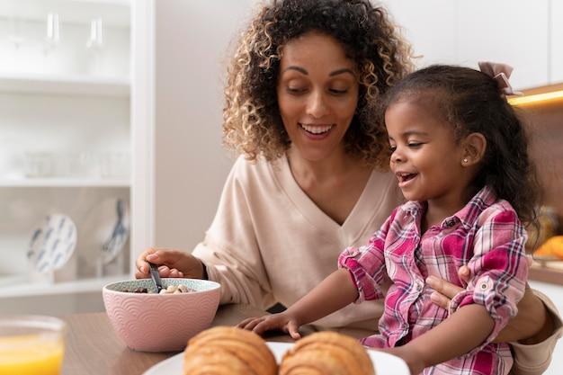 Mãe alimentando a filha na cozinha