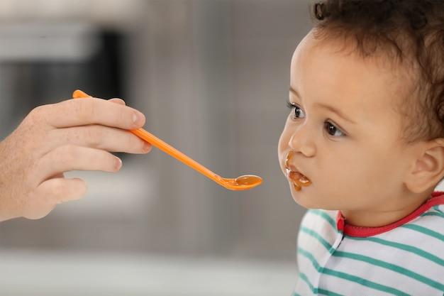 Mãe alimentando bebê com colher dentro de casa