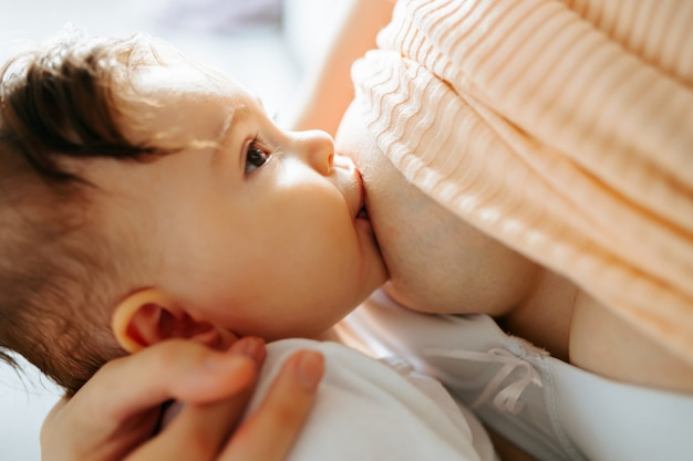 Mãe alimentando bebê em casa amamentando mãe com criança jovem mulher amamentando e alimentando b.