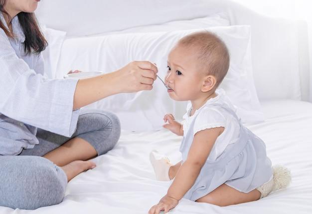 Mãe alimentando frutas para sua menina criança na cama