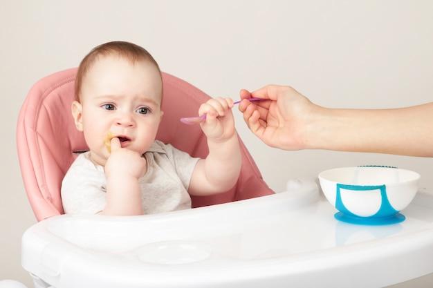 Mãe, alimentando seu bebê bonito na cadeira em fundo cinza.