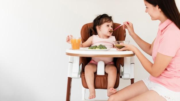 Mãe alimentando sua filha fofa