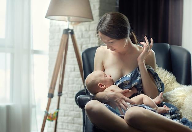 Mãe amamentando a criança à tarde, sentado em uma cadeira