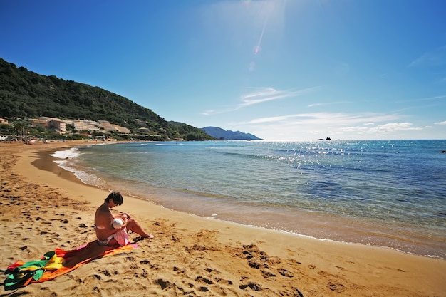 Mãe amamentando uma criança na praia
