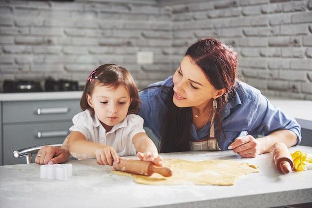 Mãe amando o forno para a filha do biscoito.