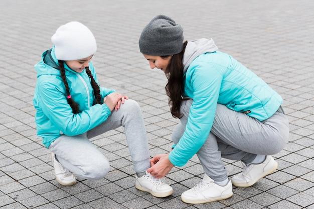 Mãe amarrar cadarços de sapato para filha