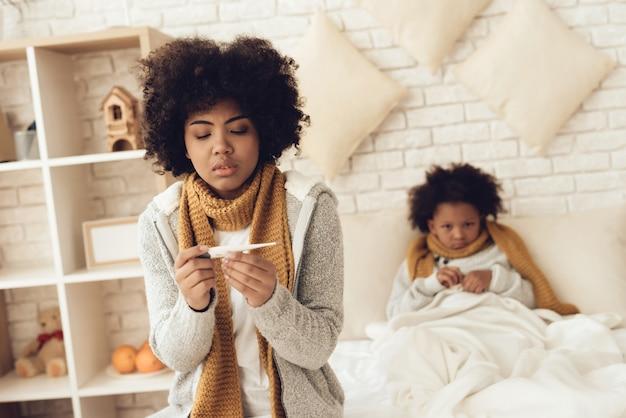 Mãe americana e filha que sentam-se na cama em casa.
