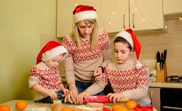 Mãe amigável e filhos fazendo bolos caseiros de casa de pão de gengibre