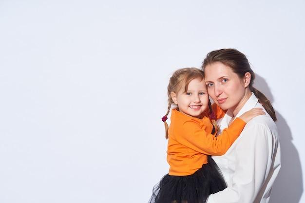 Mãe amorosa abraça a menina, segurando-a firmemente nos braços