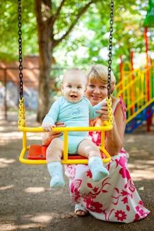 Mãe amorosa abraça seu filho pequeno no playground. retrato de uma linda mãe com bebê